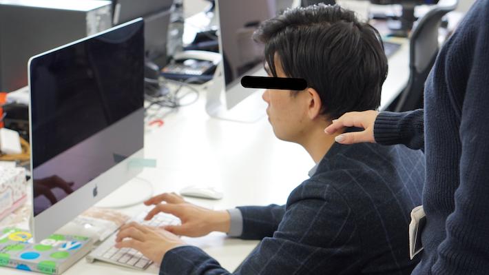 パソコンに向かうライターに伸びる女性の手